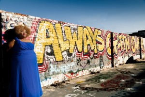 Plus size African American woman with a blue bridesmaid dress on standing next to a graffiti wall.