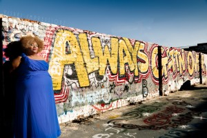 Black plus size woman in a blue bridesmaid dress standing in front of a graffiti wall that says always getting over.